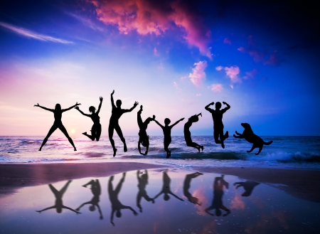 Happy people and dog jumping together on the sunset beach Stock Photo - 12504709