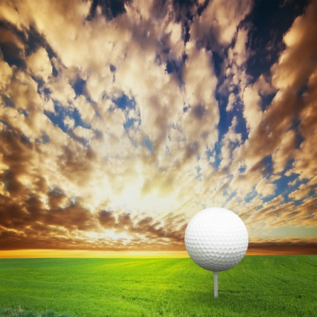Playing golf  Ball on tee, green golf field at sunset photo