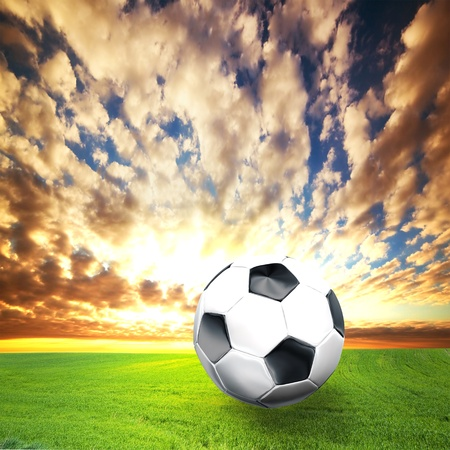 Football, soccer ball on green grass at sunset photo