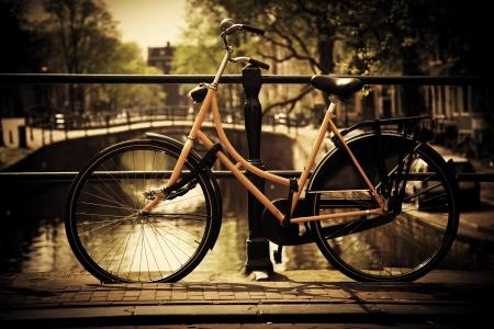 bicicleta retro: Amsterdam, Holanda, Países Bajos. Puente del canal romántico, retro moto. Casco antiguo