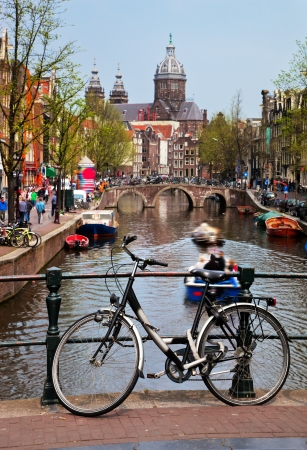 Amsterdam, Holland, Netherlands. Church of St Nicholas, old town canal, boats, bike photo