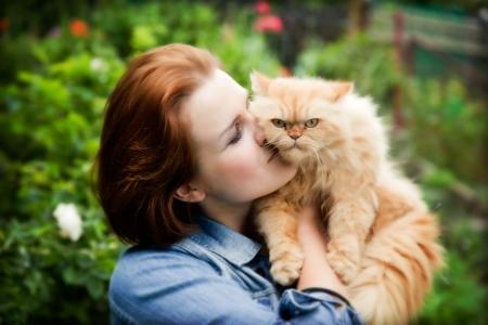gato jugando: Mujer joven con el juego del gato persa. Retrato al aire libre