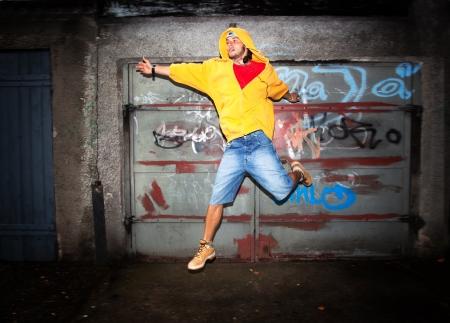 Young man jumping  dancing on grunge graffiti wall background photo