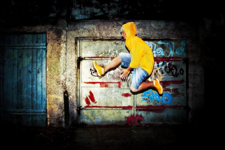 street dance: Young man jumping  dancing on grunge graffiti wall background Stock Photo