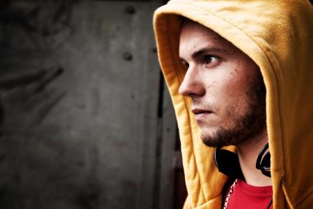 sudadera: Retrato de hombre joven en sudadera con capucha  grunge puente en la pared de graffiti