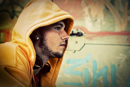 niño en patines: Joven retrato de perfil en la sudadera con capucha  grunge puente en la pared de graffiti