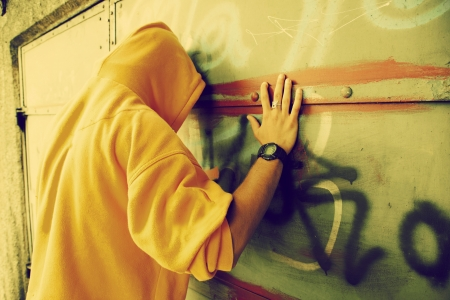 Young man in hooded sweatshirt  jumper facing grunge graffiti wall. Conceptual photo