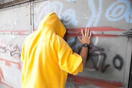 Young man in hooded sweatshirt / jumper facing grunge graffiti wall. Conceptual photo