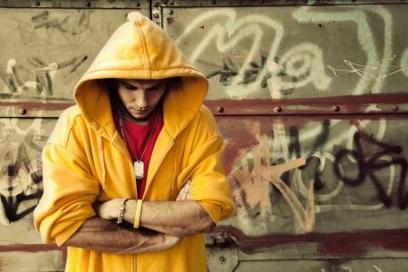adolescencia: Retrato de hombre joven en sudadera con capucha  grunge puente en la pared de graffiti