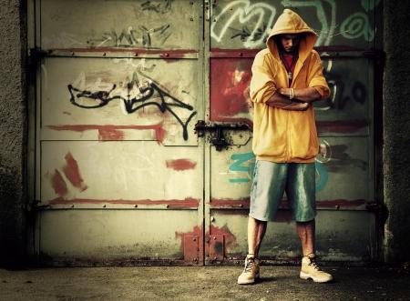 hoody: Молодой человек портрет в капюшоном  перемычки на гранж граффити стены Фото со стока