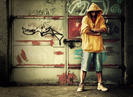 Young man portrait in hooded sweatshirt / jumper on grunge graffiti wall photo