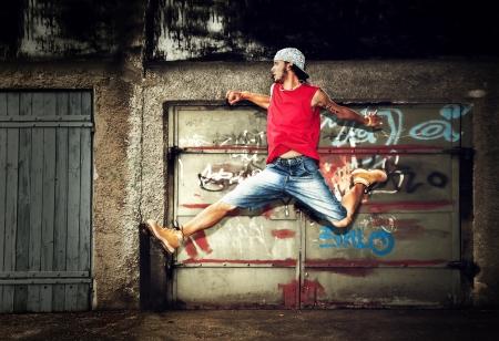 niño en patines: Hombre joven que salta  bailando sobre fondo grunge pared de graffiti Foto de archivo