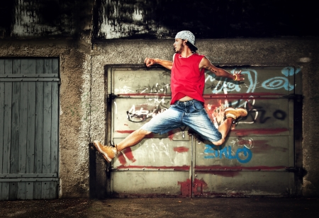 grafitis: Hombre joven que salta  bailando sobre fondo grunge pared de graffiti Foto de archivo