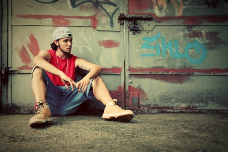 street fashion: Young man sitting portrait on grunge graffiti wall