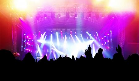 concerto rock: Las personas con las manos hasta que se divierten en un concierto de música  disco partido. Foto de archivo