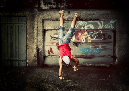 graffiti art: Young man jumping  dancing on grunge graffiti wall background Stock Photo
