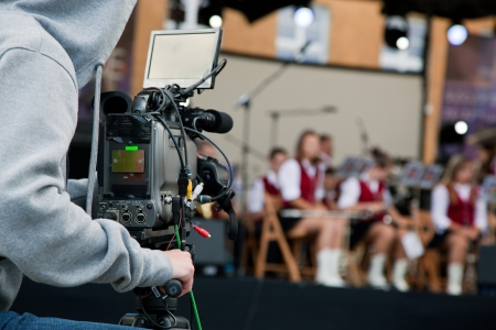live action: Video camera operator capturing performance on stage