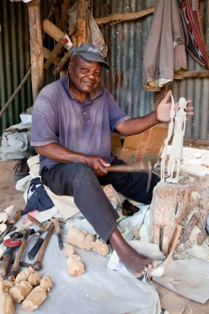 Southern part of KENYA, AFRICA - DECEMBER 10: A man carving figures in wood. Thousands of Africans in Kenya live on souvenirs handcraft. December 10, 2012 on the back of the souvenirs shop by the roadside in southern Kenya.