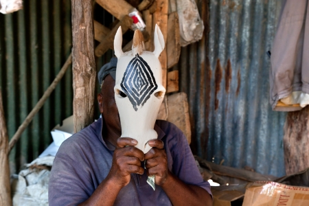 Southern part of KENYA, AFRICA - DECEMBER 10: A man works in a souvenirs workshop, carving figures in wood. Thousands of Africans in Kenya live on souvenirs handcraft. December 10, 2012 on the back of the souvenirs shop by the roadside in southern Kenya.