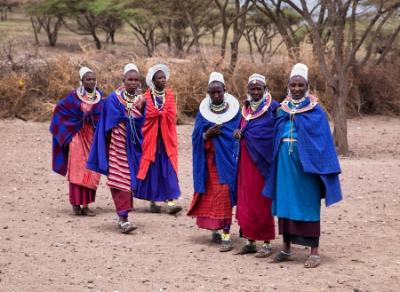 Maasai village, TANZANIA, AFRICA - DECEMBER 11: A group of Maasai women in traditional clothes in front of their village on December 11, 2012 in Tanzania. Maasai are one of the best known ethnic groups in Africa living in their traditional old way.