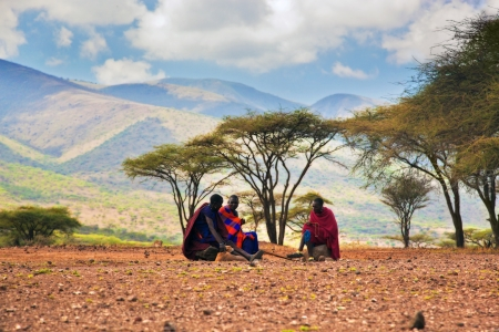 Ngorongoro Conservation Area, TANZANIA, AFRICA - DECEMBER 11: Three Maasai men in traditional clothes sitting on savannah landscape background on December 11, 2012 in Tanzania. Maasai people are among the best known of African ethnic groups located in Ken