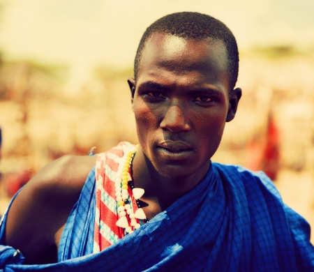 Maasai village, TANZANIA, AFRICA - DECEMBER 11: Maasai young adult man portrait in traditional clothes on December 11, 2012 in Ngorongoro Tanzania. Maasai people are among the best known of African ethnic groups located in Kenya and northern Tanzania.