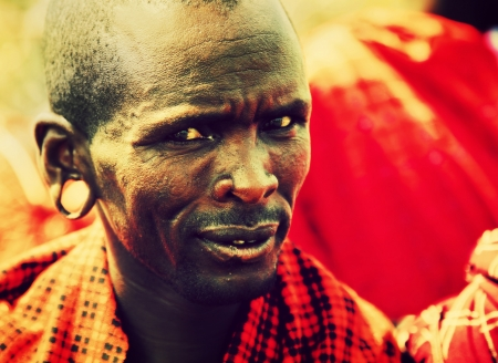 Maasai village, TANZANIA, AFRICA - DECEMBER 11: Maasai middle aged man portrait in traditional clothes on December 11, 2012 in Ngorongoro Tanzania. Maasai people are among the best known of African ethnic groups located in Kenya and northern Tanzania.