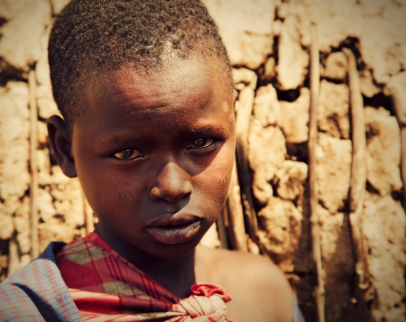 Maasai village, TANZANIA, AFRICA - DECEMBER 11: Maasai child, boy portrait in traditional clothes on December 11, 2012 in Ngorongoro Tanzania. Maasai people are among the best known of African ethnic groups located in Kenya and northern Tanzania.