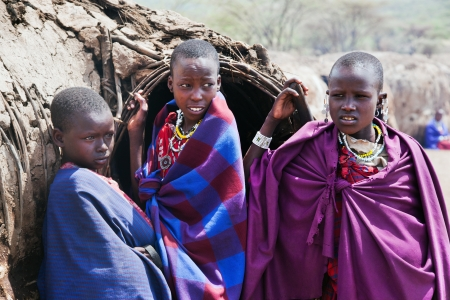 Maasai village, TANZANIA, AFRICA - DECEMBER 11: Maasai children portrait in front of their hut in traditional clothes on December 11, 2012 in Ngorongoro Tanzania. Maasai people are among the best known of African ethnic groups located in Kenya and norther
