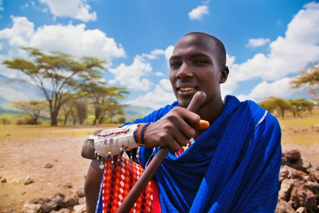 adult kenya: Maasai village, TANZANIA, AFRICA - DECEMBER 11: Maasai young adult man portrait in traditional clothes on December 11, 2012 in Ngorongoro Tanzania. Maasai people are among the best known of African ethnic groups located in Kenya and northern Tanzania.