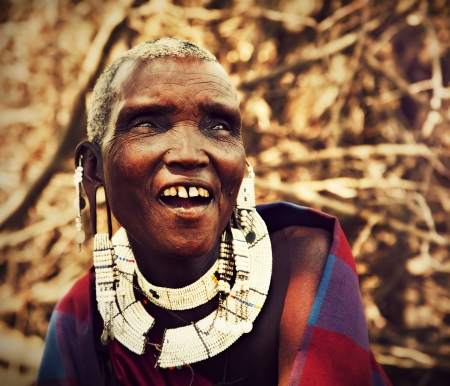 Maasai village, TANZANIA, AFRICA - DECEMBER 11: Maasai old woman laughing portrait in traditional clothes on December 11, 2012 in Ngorongoro Tanzania. Maasai people are among the best known of African ethnic groups located in Kenya and northern Tanzania. Stock Photo - 17201944