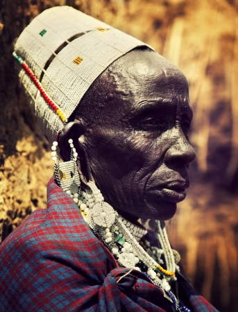Maasai village, TANZANIA, AFRICA - DECEMBER 11: Maasai old woman laughing portrait in traditional clothes on December 11, 2012 in Ngorongoro Tanzania. Maasai people are among the best known of African ethnic groups located in Kenya and northern Tanzania.