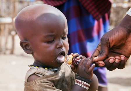 Maasai village, TANZANIA, AFRICA - DECEMBER 11: Maasai child trying a Chupa Chups lollipop which has been given by tourists on December 11, 2012 in Ngorongoro Tanzania. Maasai people live their traditional uncivilized way and sometimes tourist offer them  Stock Photo - 17202006