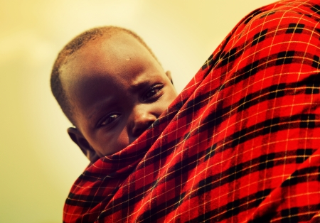 Maasai village, TANZANIA, AFRICA - DECEMBER 11: Maasai crying baby carried by his mother on December 11, 2012 in Ngorongoro Tanzania. Maasai people are among the best known of African ethnic groups located in Kenya and northern Tanzania.