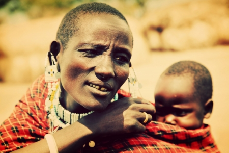 Maasai village, TANZANIA, AFRICA - DECEMBER 11: Maasai crying baby carried by his mother on December 11, 2012 in Ngorongoro Tanzania. Maasai people are among the best known of African ethnic groups located in Kenya and northern Tanzania. Stock Photo - 17202010