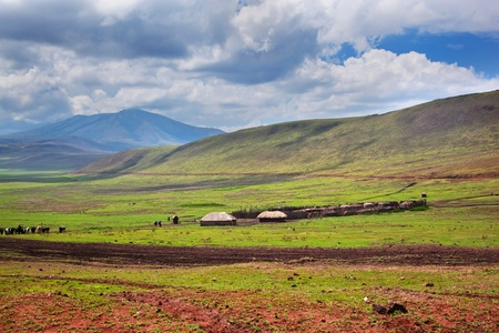 Savannah landscape in Tanzania, Africa. Maasai houses in the valley photo