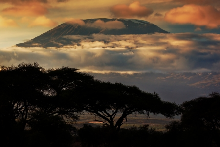 kenya: Mount Kilimanjaro and clouds line at sunset, view from savanna landscape in Amboseli, Kenya, Africa