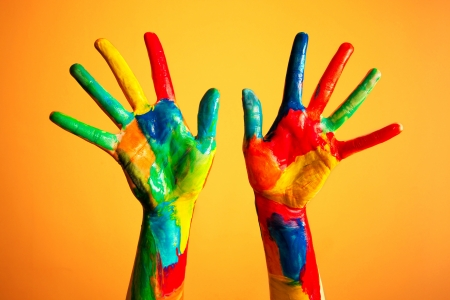 Painted hands, colorful fun. Creative, funny and artistic means happy! Orange background wall photo