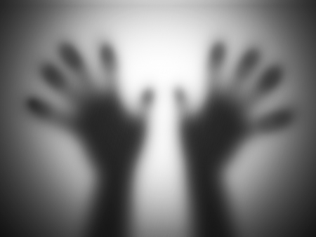 Hands silhouettes touching blurry glass screaming for help. Concepts for nightmare, panic, violence etc. photo