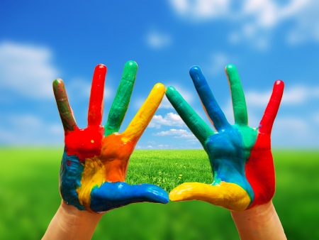 2 way: Painted colorful hands showing way to clear happy life, conceptual. Sunny perfect landscape