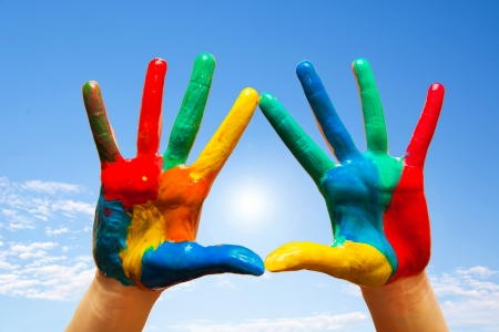 Painted hands, colorful fun. Creative, funny and artistic means happy! Blue sky background photo
