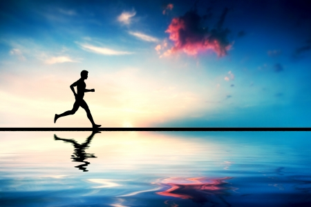 アスリート: 日没で走っている男のシルエット。水の反射