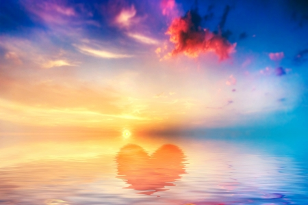 gods love: Hearth shape in calm ocean at sunset. Beautiful sky, clouds and colors