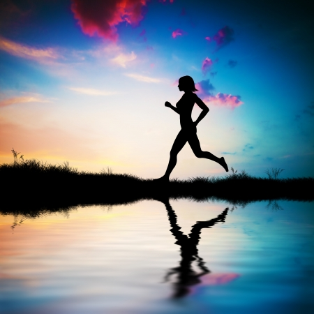 Silhouette of a fit woman running at sunset. Water reflection