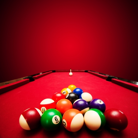 Billards pool game. Color balls in triangle, aiming at cue ball. Red cloth table photo