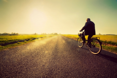 retirement: Old man riding a bike on asphalt road towards the sunny sunset sky