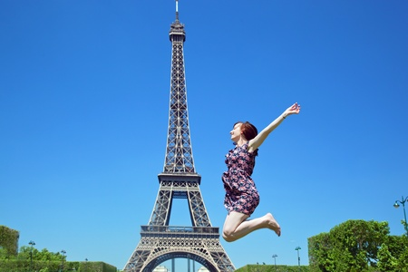 Young attractive happy woman jumping for joy against Eiffel Tower in Paris, France photo