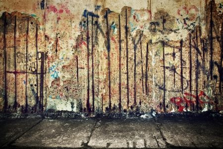 Grunge, roestige betonnen muur met willekeurige graffiti en betonnen vloer. Grunge achtergrond