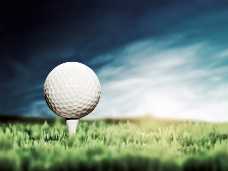Golf ball placed on white golf tee on green grass golf course  Moody sunny sky