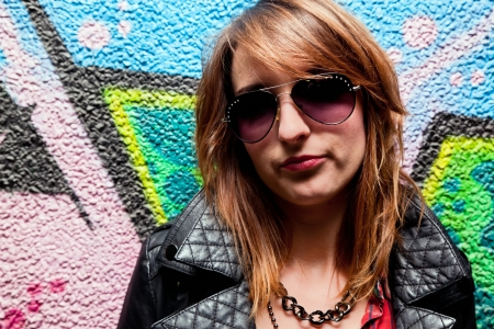 subculture: Stylish fashionable girl posing against colorful graffiti wall. Fashion, trends, subculture Stock Photo